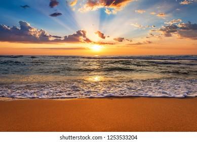 Salida del sol colorida de la playa del océano con el cielo azul profundo y los rayos del sol.