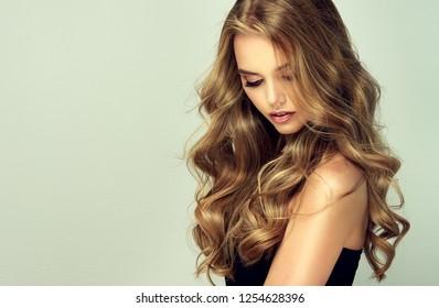 Lachend blond meisje met lang en glanzend golvend haar. Mooi glimlachend vrouwenmodel met krullend kapsel.