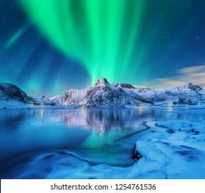 Aurora borealis über schneebedeckten Bergen, gefrorener Seeküste und Reflexion im Wasser in den Lofoten-Inseln, Norwegen. Nordlichter. Winterlandschaft mit Polarlichtern, Eis im Wasser. Sternenhimmel mit Aurora