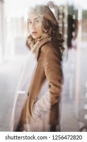 Attraktive Frau in totalem Beige-Look trägt Baskenmütze und Mantel. Lockige haare. Frau unter dem Glas des Fensters. Mädchen schaut in die Kamera. Foto im Stil des alten Films.
