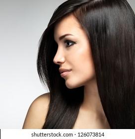 長い茶色の髪のきれいな女性。スタジオでポーズをとるファッションモデルのプロフィールの肖像画。