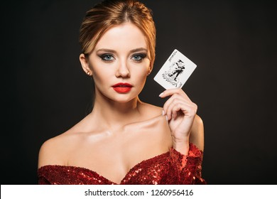attractive girl in red shiny dress holding joker card and looking at camera isolated on black