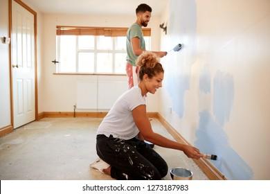 一緒に新しい家の絵画の壁の部屋を飾るカップル