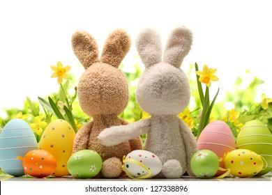 Osterdekoration mit Zuckerkaninchen, Eiern und Blumen.