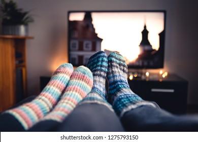 冬にテレビで映画やシリーズを見ている靴下やウールのストッキングとカップル。テレビのオンラインストリーミングサービスを使用して、自宅のリビングルームのソファのソファに座っているか横になっている女性と男性