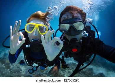 Disparar bajo el agua de una joven pareja buceando con buceo en un mar tropical y mostrando una señal de ok