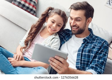 Hombre barbudo y niña en casa tiempo en familia sentado en el piso en la alfombra padre sosteniendo tableta digital viendo video en línea sonriendo alegre primer plano