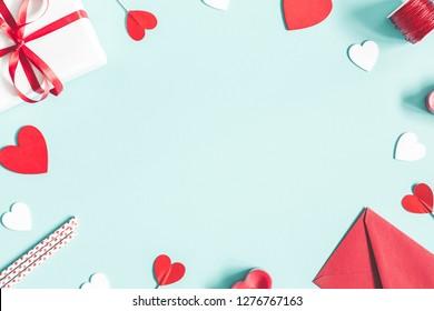 バレンタインデーの背景。パステルブルーの背景にギフト、キャンドル、紙吹雪、封筒。バレンタインデーのコンセプト。フラットレイ、上面図、コピースペース