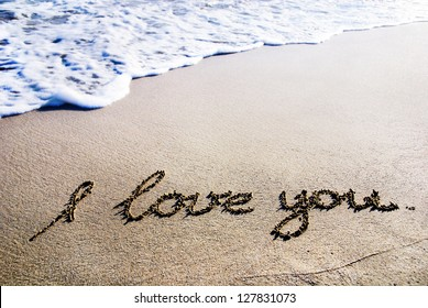 """words """"I love you"""" outline on the wet sand with the wave brilliance"""