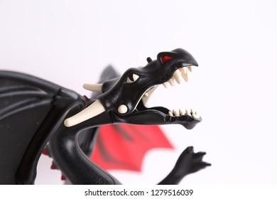 schwarzes und rotes Drachenspielzeug auf weißem Hintergrund