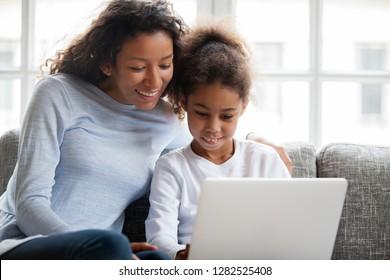 La madre y la hija afroamericanas sonrientes se divierten comprando en línea en casa, una madre negra feliz enseñando a una niña pequeña de raza mixta a aprender a usar la computadora portátil, ver dibujos animados, hacer videollamadas en la computadora