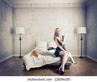 ベッドの上に座っている若いエレガントな女性