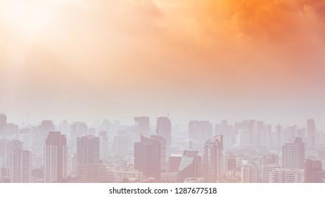 Stadtlandschaft im Dunst mit orange bewölktem Himmel, stark verschmutzte Stadt, Umweltverschmutzung