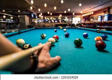 Mano con cue apuntando a la bola de billar en la mesa