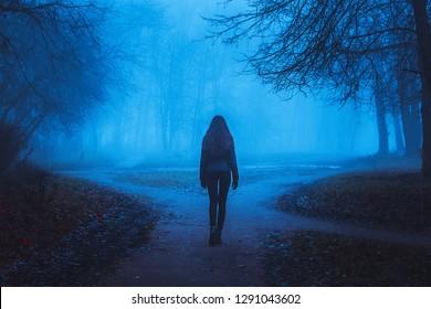 Mädchen geht auf der Straße in einem geheimnisvollen Wald. Hintergrund für Tapeten. Seltsamer Wald im Nebel mit roten Blättern. Mystische Atmosphäre. Dunkler gruseliger Park. Paranormal eine andere Welt.