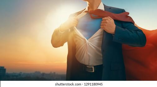 Superheld-Geschäftsmann, der die Skyline der Stadt bei Sonnenuntergang betrachtet. das Konzept von Erfolg, Führung und Sieg im Geschäft.