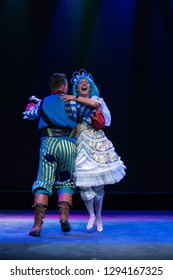 Actor in a pirate costume and actress in a princess costume play a performance for children on the theater stage