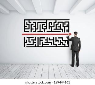 白い壁に迷路を描く実業家