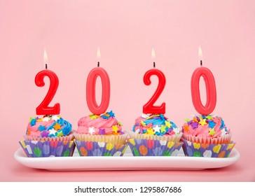 Weiße Cupcakes mit regenbogenfarbenem Zuckerguss und bunten Sternbonbons auf einem rechteckigen rosa Hintergrund der Platte mit 2020 brennenden Kerzen. Frohes Neues Jahr Thema.