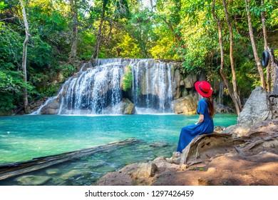 Frau, die am Erawan-Wasserfall in Thailand sitzt. Schöner Wasserfall mit smaragdgrünem Pool in der Natur.