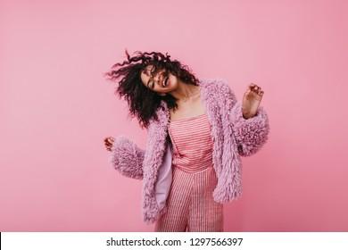 Incendiaria chica fantásticamente hermosa en abrigo de piel ecológica se mueve divertido. Imagen de dama encantadora en ropa rosa