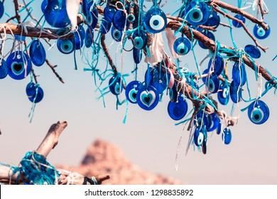 Ojos azules del mal de ojo, un símbolo nacional y guardián en Turquía. Muchos ojos redondos y azules cuelgan de un árbol, que es protección contra lo malo. Hermoso panorama del cañón en el fondo.