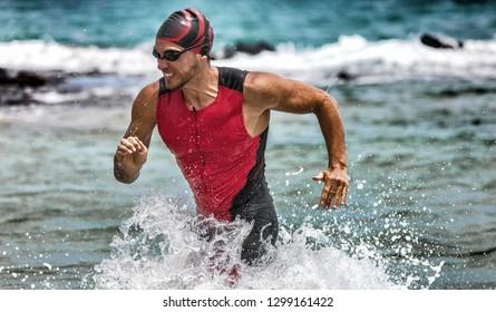 アイアンマンレース中に水が不足しているトライアスロンスイミング男。男性トライアスリートが泳ぐ時間の競争を終えます。プロのトライスーツで水から決定されたアスリートスイマースプリントを合わせます。