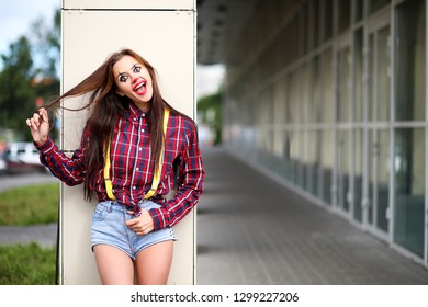 Cute girl in a clown makeup on a background of a fair and steps