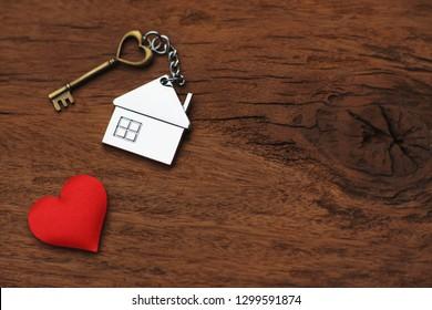 ウッドテクスチャ背景、甘い家のコンセプト、コピースペースにミニの赤いハートで飾られた家の鍵リングを持つ家の鍵