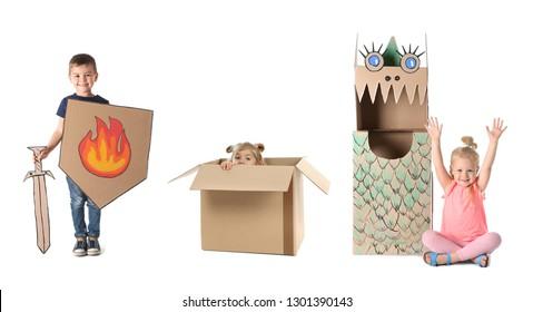 白い背景の上の段ボール箱で遊んでいる小さなかわいい子供たち。手作りのおもちゃやコスチューム