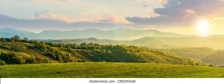 Panorama der rumänischen Landschaft bei Sonnenuntergang im Abendlicht. wunderbare Frühlingslandschaft in den Bergen. Grasfeld und sanfte Hügel. ländliche Landschaft