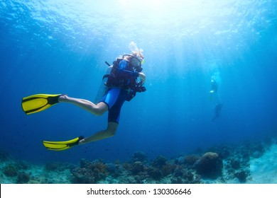 Disparar bajo el agua de buzos nadando en un agua azul claro