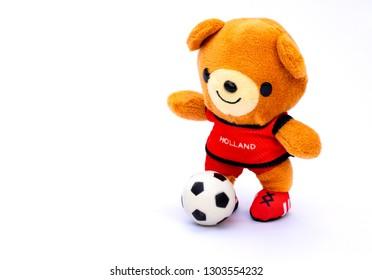 Atleta de oso de peluche jugador de España con balón aislado sobre fondo blanco.