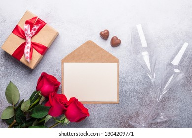 Red rose flowers bouquet, envelope, gift box, chocolate sweets on stone background Valentine's day greeting card Copy space Top view