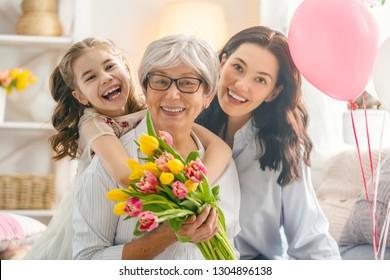 Alles Gute zum Tag der Frauen! Kind Tochter gratuliert Mutter und Oma und gibt ihnen Blumen Tulpen. Oma, Mutter und Mädchen lächeln und umarmen sich. Familienurlaub und Zusammensein.