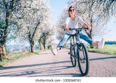 Glückliche lächelnde Frau spreizt fröhlich Beine auf Fahrrad auf der Landstraße unter Blütenbäumen. Der Frühling kommt Konzeptbild.