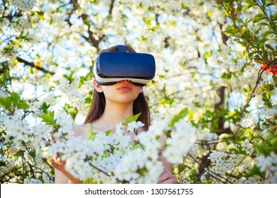 Gaming and entertainment. Virtual technology simulation. Young lady wear vr glasses in spring bloom. Cute girl play in spring garden. Pretty girl in virtual reality headset. Innovative vr technology.