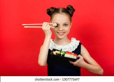 Cute smiling little girl with with sushi on  red background.  Student child girl eating sushi and rolls - commercial concept.