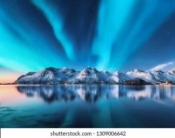 Aurora boreal y montañas cubiertas de nieve en las islas Lofoten, Noruega. Aurora boreal. Cielo estrellado con luces polares y rocas nevadas reflejadas en el agua. Paisaje de invierno nocturno con aurora, mar. Naturaleza