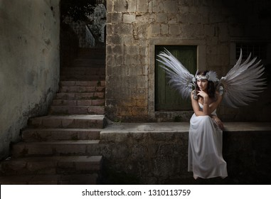 Young beautiful girl in an angel costume sitting near the house of the poor.Natural feathers and rhinestones. Conceptual image on the theme of religion and mercy.