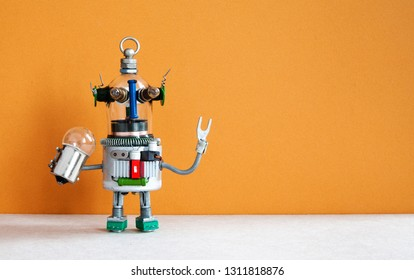 Funny robotic toy holds light bulb. creative design futuristic humanoid robot on brown gray background. copy space.