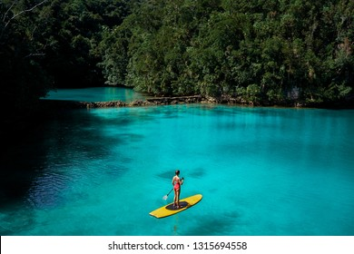 Summer holidays vacation travel. SUP Stand up paddle board. Young woman sailing on beautiful calm lagoon.