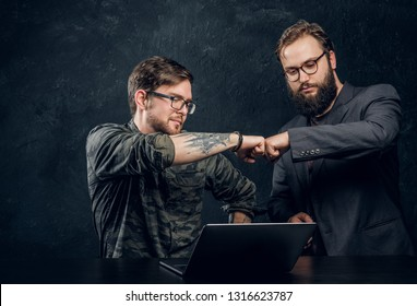 Friendship, brofist, cooperation. Two programmer's colleagues fist bumping after completion of the general project in the office against a dark wall