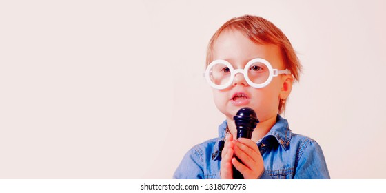 The famous actress. Humorous photo of little cute child girl singing with a microphone. Happy childhood, music, child development concept. Free space for text.