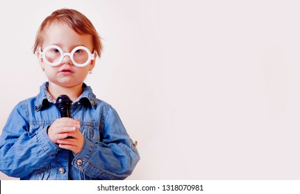 The famous actress. Humorous image of little cute child girl singing with a microphone. Happy childhood, music, child development concept.