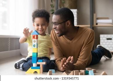 Feliz y lindo hijo jugando con papá negro niñera constructor de torre de construcción de bloques de madera multicolores, padre de familia africana y niño pequeño divirtiéndose en un piso cálido en casa