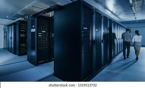 ラップトップコンピューターと若い技術者の同僚がデータセンターのサーバーラックの隣を歩いているIT管理者のショット。診断またはメンテナンスの実行。
