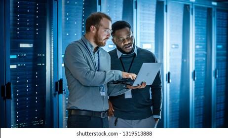 ラップトップコンピューターと黒人男性エンジニアの同僚とガラスのひげを生やしたIT技術者は、診断を実行している、またはメンテナンス作業を行っているサーバーラックの隣で作業しながらデータセンターでラップトップを使用しています