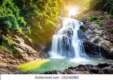 青い空と白い積雲の雲と山の美しい滝。熱帯の緑の木の森の滝。ジャングルの中を滝が流れています。自然の抽象的な背景。花崗岩の岩山。