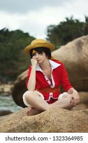 Cosplay de niño niña con sombrero de paja sentarse en una roca y pensar en la vida